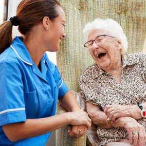 Caregiver smiling and posting with senior client