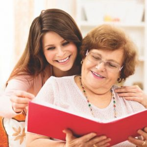 Caregiver with client reading a book