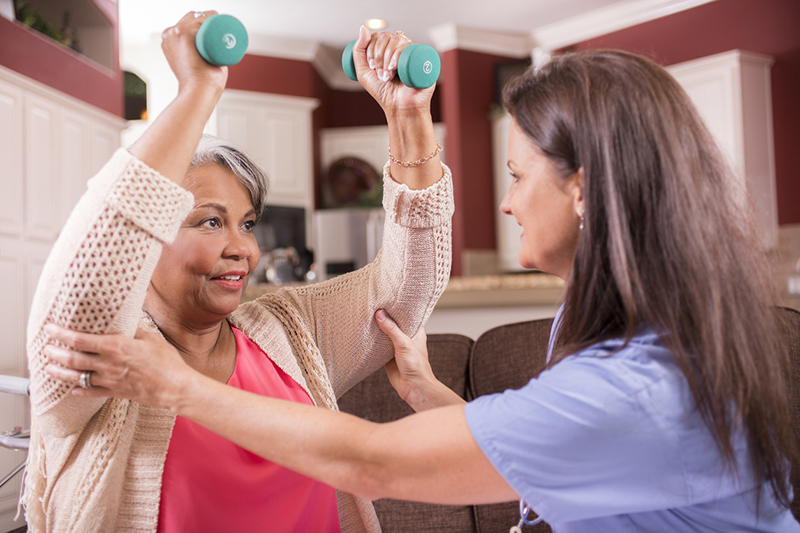 home healthcare nurse conducts physical therapy exercises with senior adult strengthening exercises using a dumbbell