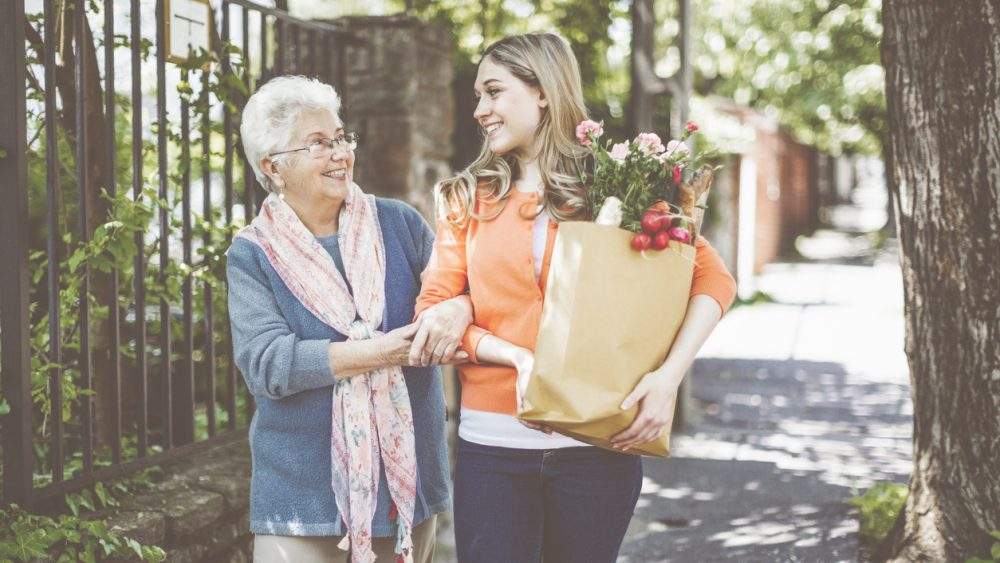 family caregiver helping senior loved one with groceries
