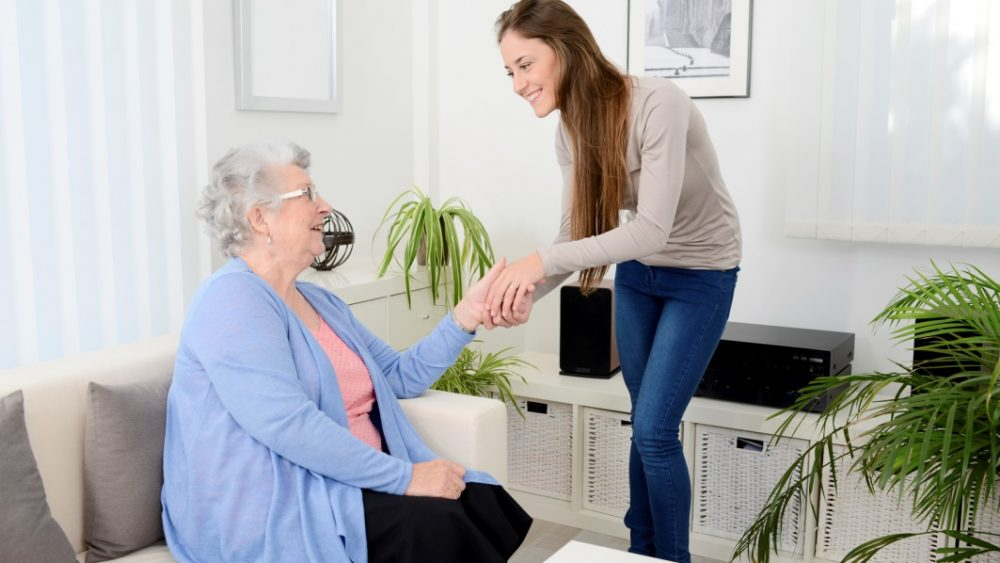 family caregiver holding hands with senior
