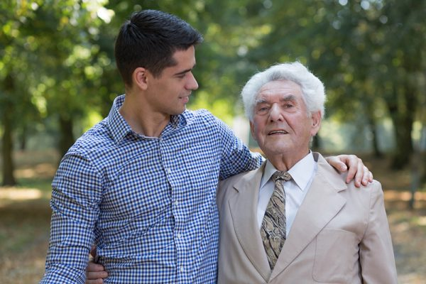 caregiver walking outside with senior man