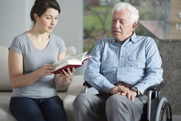 caregiver reading to elderly man in wheelchair