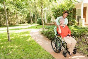 caregiver helping senior woman in wheelchair
