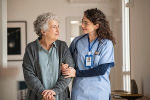caregiver assisting elderly woman walking